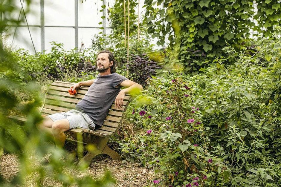 Dries Delanote op een bankje in zijn voedselbos